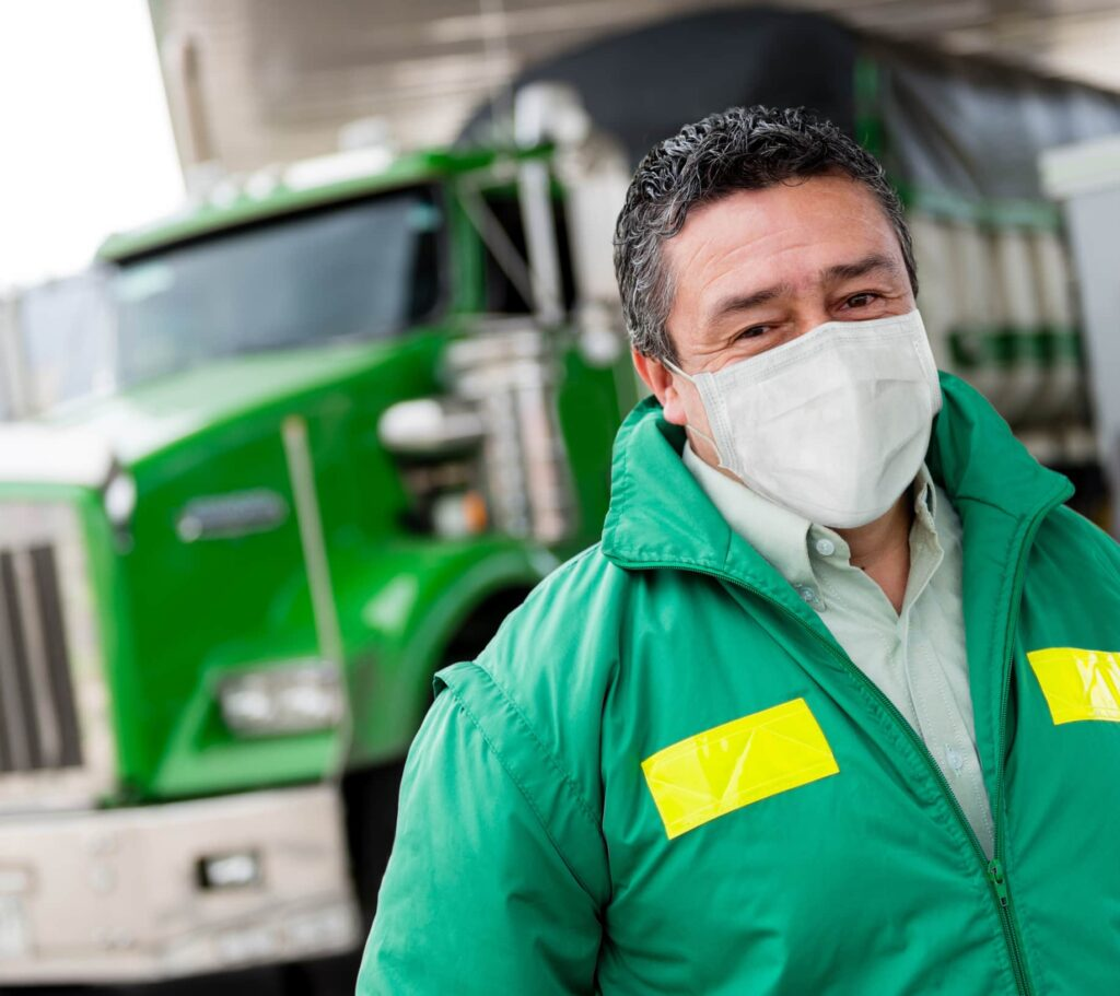Portrait of a truck driver wearing a facemask to avoid the coronavirus – pandemic lifestyle concepts