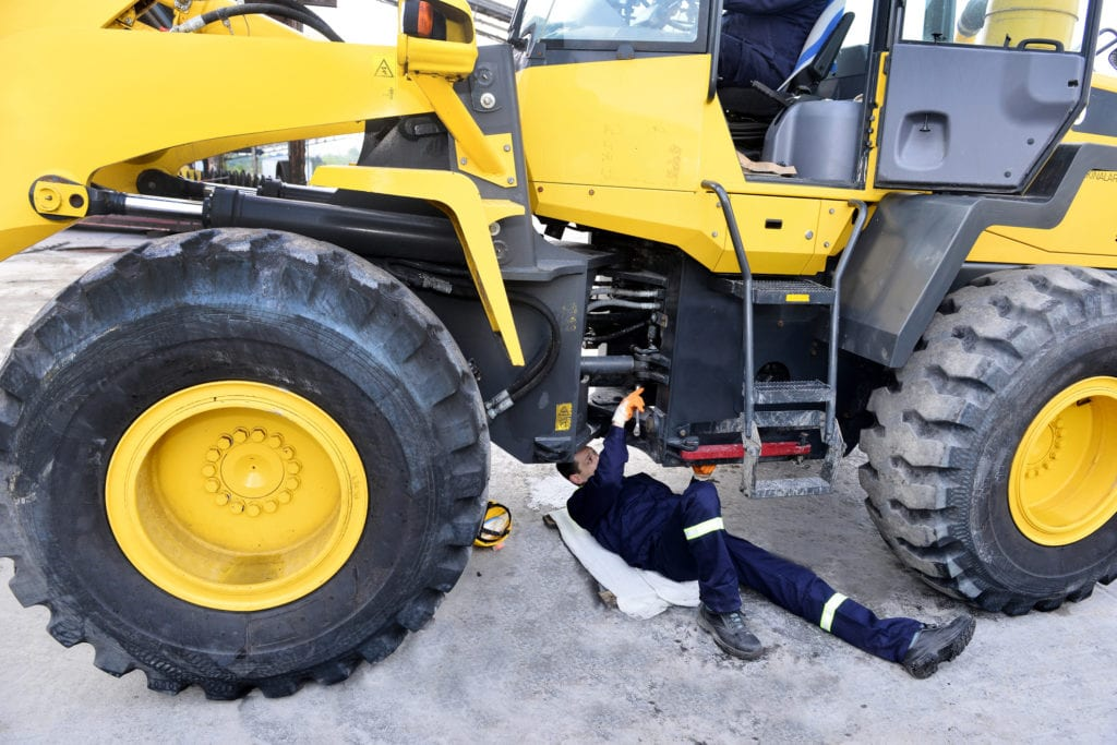 A service technician performs maintenance on an excavator.